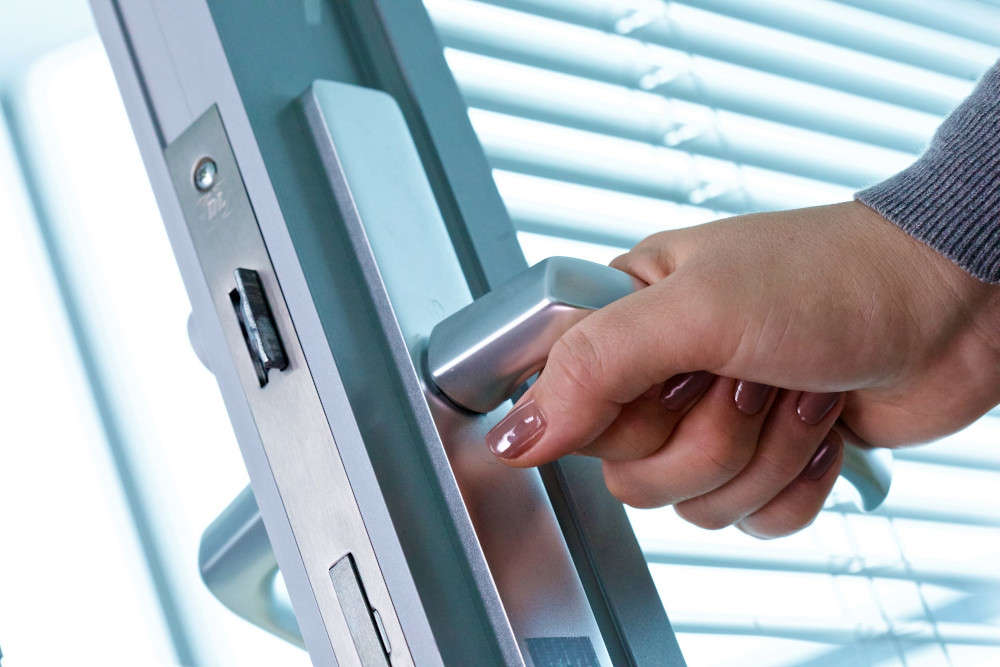 Woman's hand grasping an office door handle